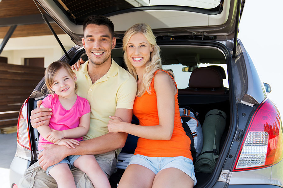 Personal Insurance - Portrait of Happy Family Sitting in the Trunk of Their Car at Home